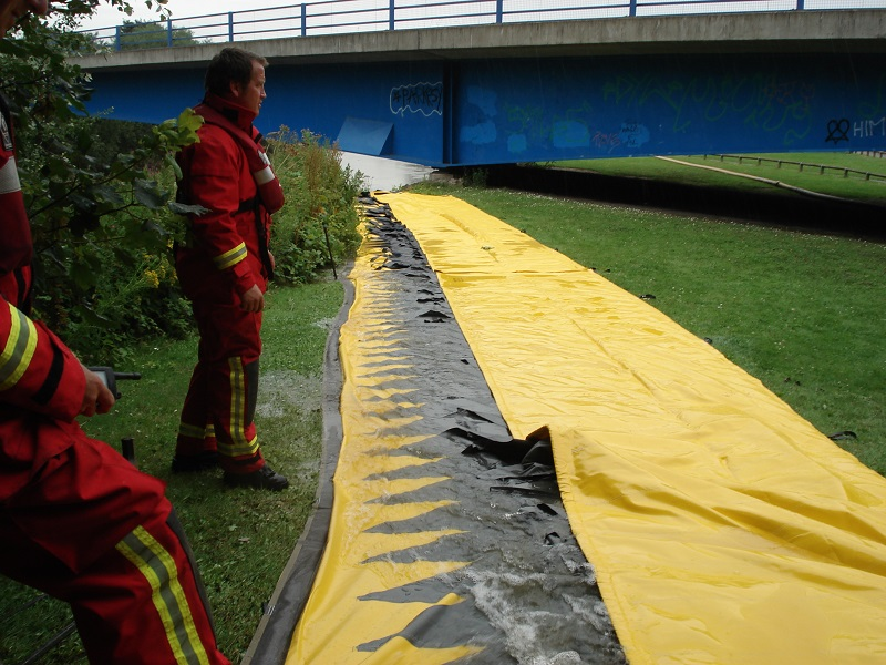 Emergency service workers setting up an alteau flood barrier by a bridge for mobile flood defence