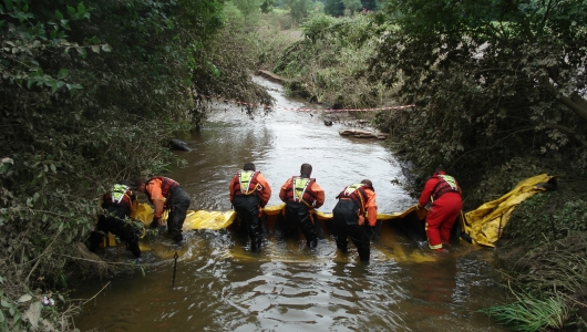 emergency servicemen setting out a alteau barrier in a flooded river