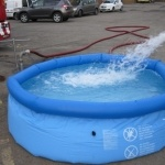 Emergency servicemen filling an aqua-sac® inflation tank with water