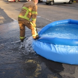 Fireman stepping on the inflation tank to drain out the water