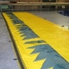 Large section of alteau flood barrier spread out over a warehouse floor